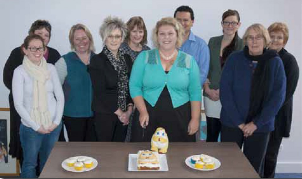 picture of Amber and the CARA team cutting an Oog cake